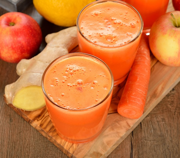 Fresh apple and carrot juice on brown background ** Note: Shallow depth of field